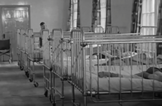 A shot of children's cots at Brockhall from the film, 'A Happy Human Being'.