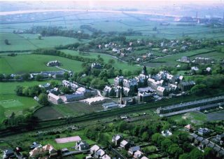 A view of the Royal Albert Hospital taken looking west. This was likely to be in the 1950s. Plenty of detail to appreciate. This includes a cricket match, the gardens and the terraced housing in the foreground is Dorrington Road, just across the rail tracks from the institution.    Frank Lord