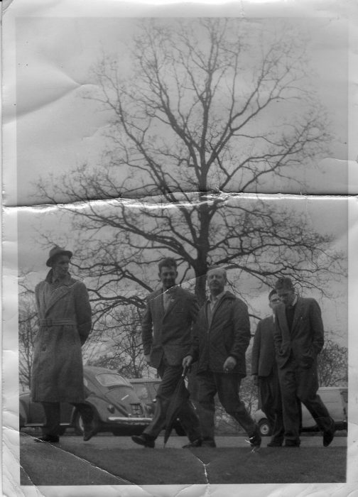 This is a photograph of men who lived in the Royal Albert. (Although, is the man with an umbrella and cigagrette a member of staff?) They are walking across the front of the institution with the photo being taken from down near the door to the 'male side'. Walter Megson, who shared this image in the early 2000s, is second from the left as you look and is likely to be in his 40s. The date of the photo is probably the 1960s.  | Walter Megson