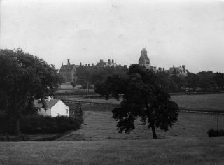 This is a view of the Royal Albert, looking south-south east. The photograph was taken from what is now (2020) the site of the Haverbreaks housing estate on the southerly edge of Lancaster. Written on the back of the photograph: '1. Royal Albert Institution'. It was only after January 20th 1910 that the institution was called this name. For many years before then it had always been called the Royal Albert Asylum. It is likely this image dates back to the 1910s. | Lancashire County Museums Service