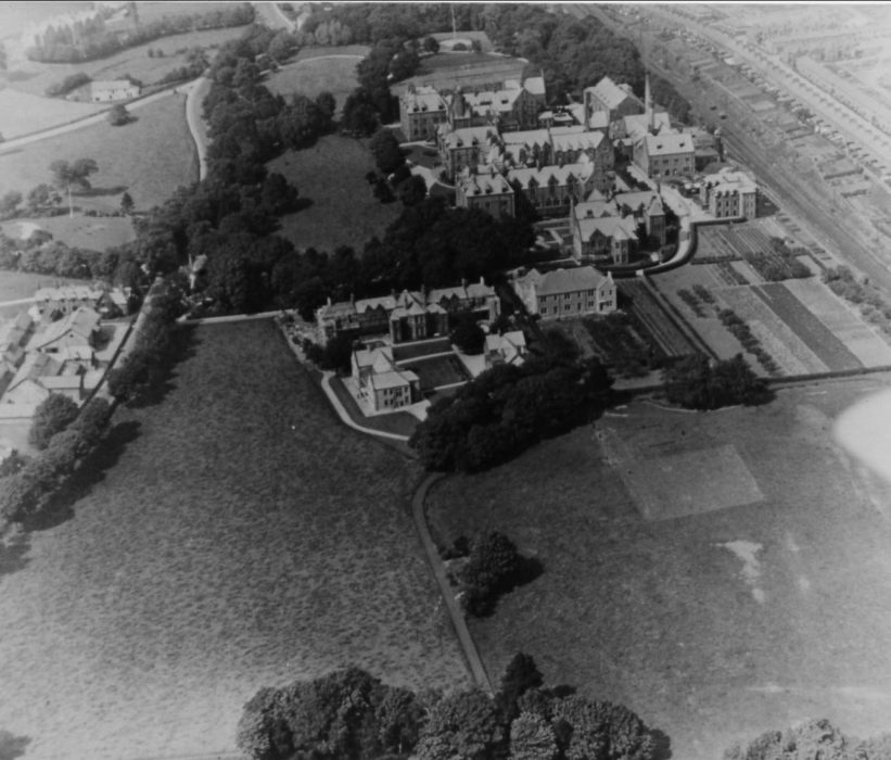 The Royal Albert Institution, possibly 1920s? (There is no sign of Barlow Home, built during the early 1930s and opened in 1935.) The view is looking North. The institution's gardens are on the right. The farm is across the road, on the left. Also on the right is the main west coast railway line, with Dorrington Road and Scotforth on the other side.  | Lancashire County Museums Service
