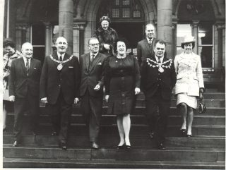 Matron Wareing leading the way, with the Medical Superintendant Dr Cunningham (1953 - 1972) to the far left of the image. They were 'dancing' down the front entrance steps of the Royal Albert cleaned by hospital residents.  | Lancashire County Museums Service