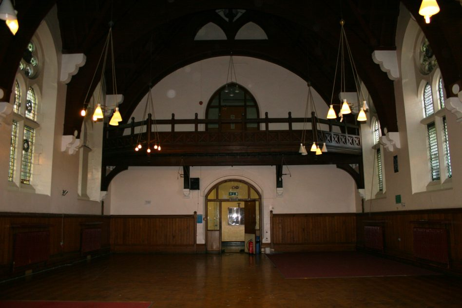 De Vitre Hall, the Royal Albert as it was in 2006, when the former institution had been an Islamic college for 10 years. This photograph is facing west towards doors leading on to the Main Corridor of the former institution. The hall's entrance was almost exactly in the middle of the Main Building of the Royal Albert,  at the point where for most of its existence it divided the female and male sides. Former residents recall men or boys coming in the dining hall from the left, and women or girls coming from the right. Recollections of former staff and residents recall that the first floor balcony in the photograph was near to the Board Room which hosted meetings for the Royal Albert's Central Committee. During their visit, members would observe the residents having their meal,  | Mandy Cody
